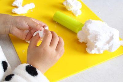 白い小麦粉粘土で遊ぶ子供の手